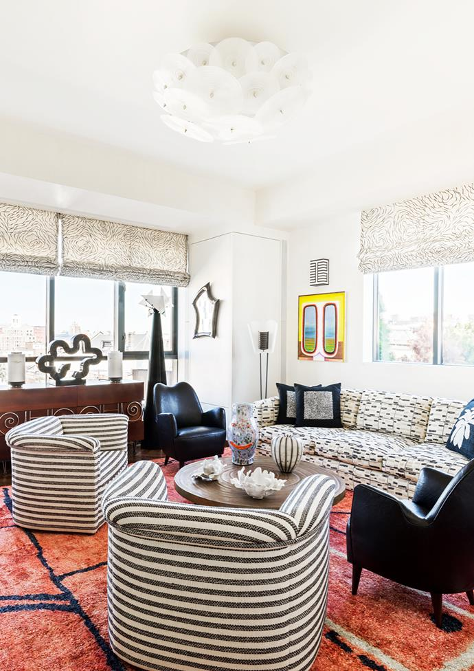 Custom Kelly Wearstler sofa in the sitting room. Striped chairs by Ward Bennett. 1960s Italian armchairs in black leather from John Salibello. Ado Chale bronze coffee table. Murano glass chandelier from a Paris flea market. Artwork is Transmission by Clint Jukkala.