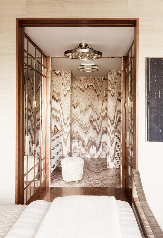 Master bathroom has 'Palissandro Tiger' marble. Ceiling light from Jean Perzel. Custom Kelly Wearstler lambswool stool.