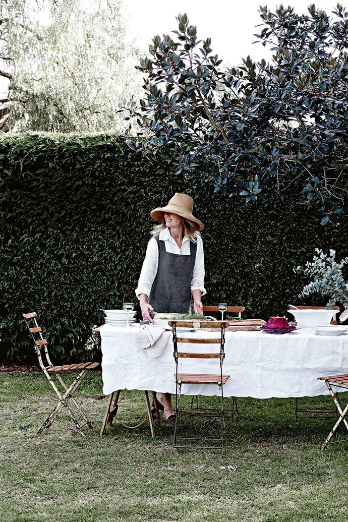 Sheltered by the tall hedge of Leyland cypress, Mickey Robertson sets a table in her Camden garden under a Port Jackson fig.