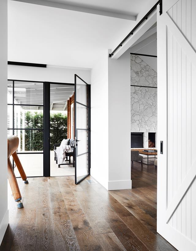 """This transition point between verandah, living room and hall in this [Mornington Peninsula home](https://www.homestolove.com.au/functional-yet-luxurious-home-on-the-mornington-peninsula-20568 target=""""_blank"""") needed a unifying element – here it's in the form of V-groove barn doors, custom made from cedar. The flooring is engineered European oak. A pommel horse is an unusual and fun touch."""