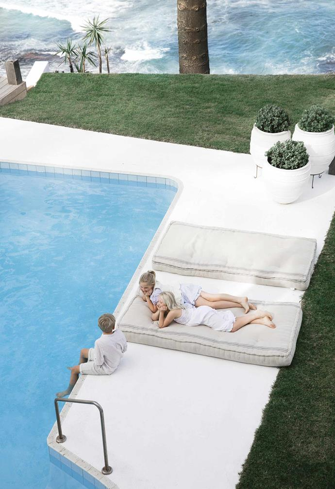 "The stark all-white palette surrounding the swimming pool in this [Mediterranean-style home](https://www.homestolove.com.au/mediterranean-style-all-white-home-16945|target=""_blank"") adds a holiday-style aesthetic to the backyard."