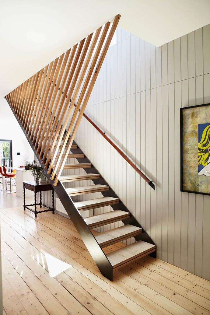 "Visible from many vantage points in the home, beautiful silver ash battens enclose the stairs in the entry hall of this Melbourne home. ""The building designer used slatted timbers extensively outside, so we used slatted timber in various forms inside,"" says interior designer Michelle Skinner of Designmas. The artwork is by Roy Eden."