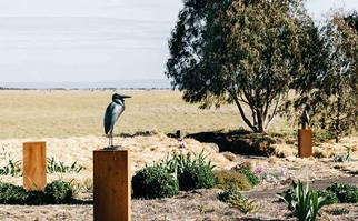 Bird sculpture on a pedestal in a garden