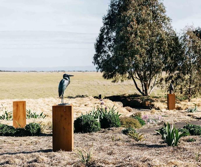 Bird sculpture on a pedestal in a garden