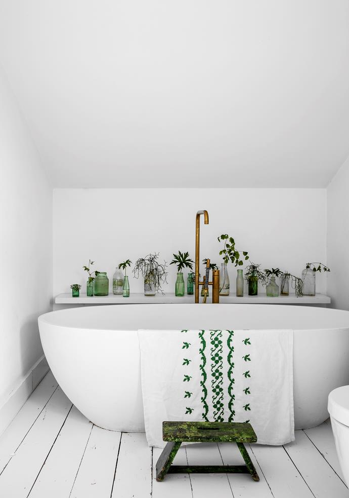 White floorboards and a deep C.P. Hart tub with Vola tapware evokes a meditative mood in the bathroom. Colour comes from the foot stool, bathmat and green glass bottles collected from Sunbury Market and all over Paris.