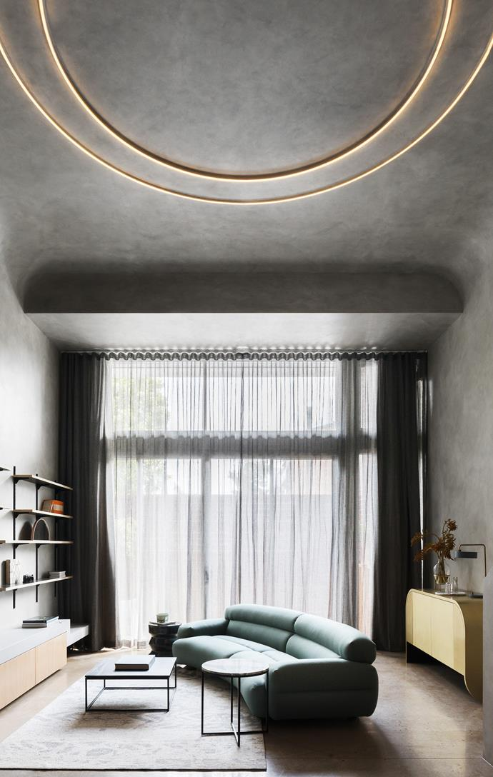 Sheer, slate-coloured curtains diffuse the light in the living room, while two circular pendants emit a warm glow. A pale green Jardan 'Valley' sofa and brass sideboard from Jonathan West break up the moody grey scheme.