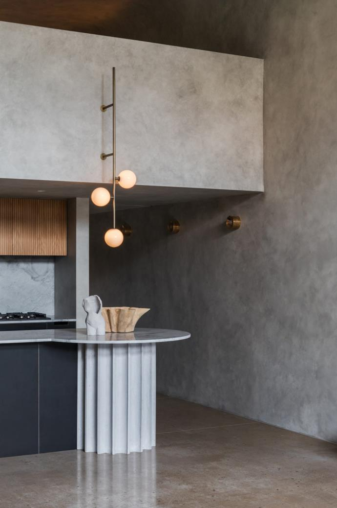 In a raw and imposing space such as this, softness is key, and can be achieved without resorting to the usual cushions and throws. Curved, organic surfaces will instantly soften a space, as will warm lighting.