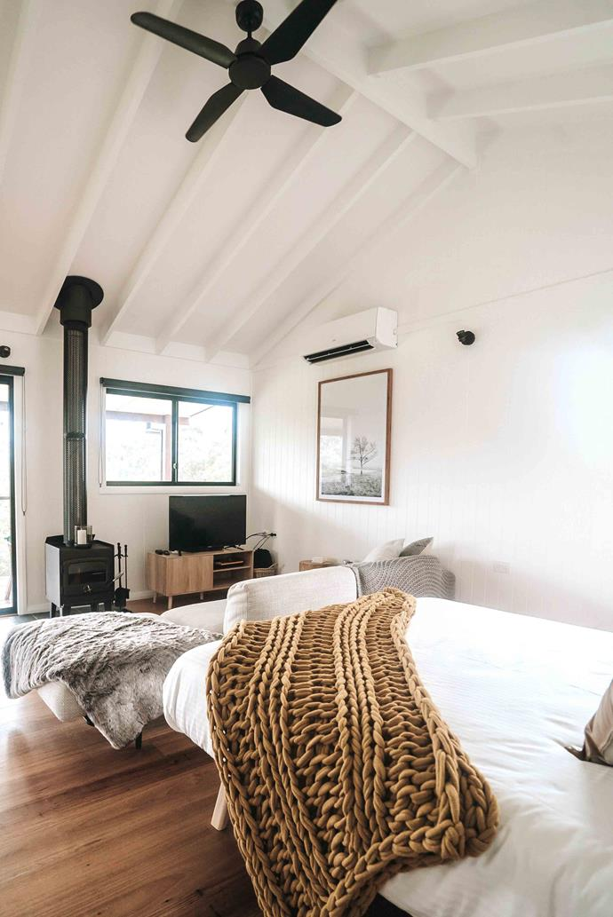 """An open plan living room and bedroom with a fireplace. [Cathedral ceilings](https://www.homestolove.com.au/exposed-ceiling-beams-17206 target=""""_blank"""") create a sense of spaciousness while the wood burning fireplace adds warmth and charm."""