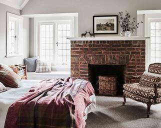 Modern country bedroom with red brick fireplace