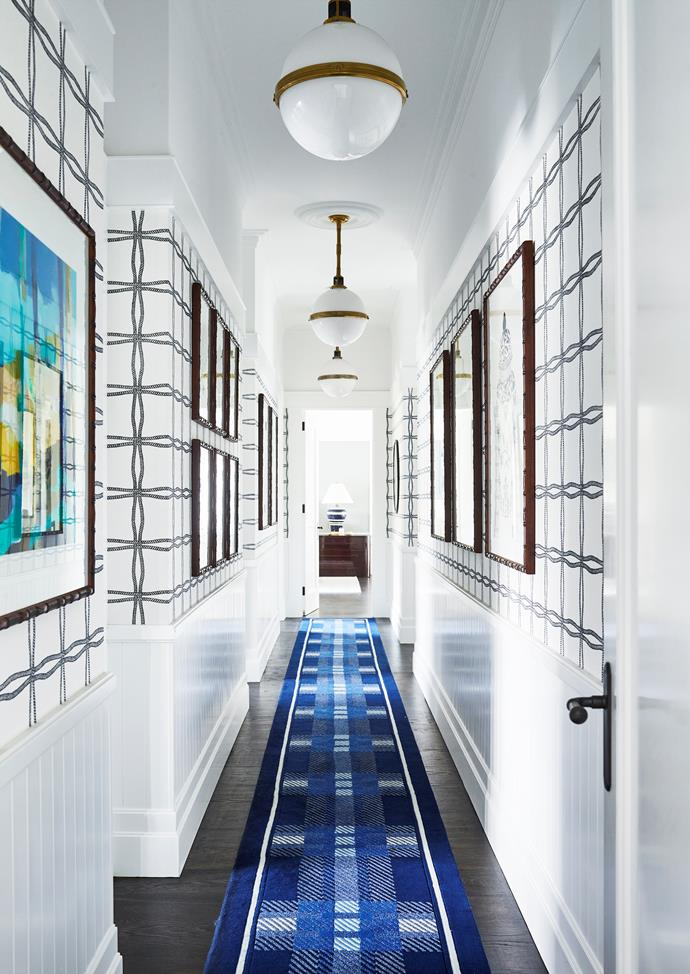 Artworks line the hallway, including Ginger Jar IV in Indigo (right), Minnamurra (left), both by Designer Boys from Boyd Blue. Custom plaid runner from Designer Rugs. Phillip Jeffries wallpaper from The Textile Company. 'McCarren' globe pendant lights from Ralph Lauren. Photograph by Anson Smart.