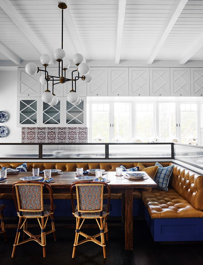 'Bistro' 12-light chandelier from RH hangs over banquette seating abutting the kitchen island. 17th-century monastery dining table from RH with dining chairs from Maison Drucker, Paris. Photograph by Anson Smart.
