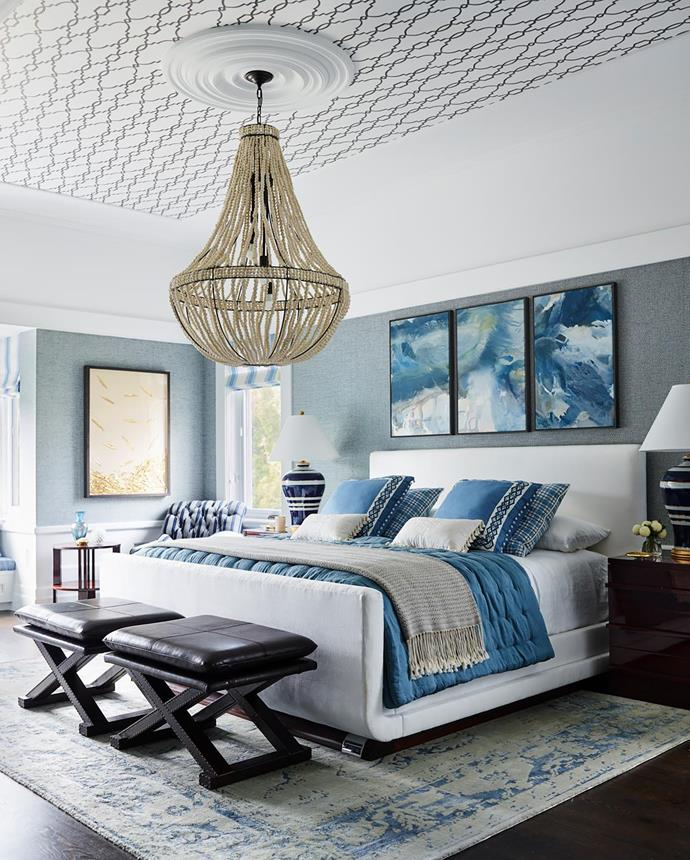 At the foot of the Ralph Lauren 'Cote D'Azur' king bed in the main bedroom are leather 'X-Base' stools from RH. 'Delphine' table lamps on 'Cote D'Azur' bedside chests, all from Ralph Lauren. Above the bed hangs Trust by Scott Petrie. 'Empire' chandelier and 'Arte' rug from RH. Blind in Chivasso 'Pacific Cruiser' from Unique Fabrics. Ceiling in Cole & Son 'Folie Parterre' wallpaper from Radford Furnishings. Artwork on far wall from Natural Curiosities. Photograph by Anson Smart.