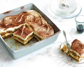 Tiramisu in a tray with a slice on a plate