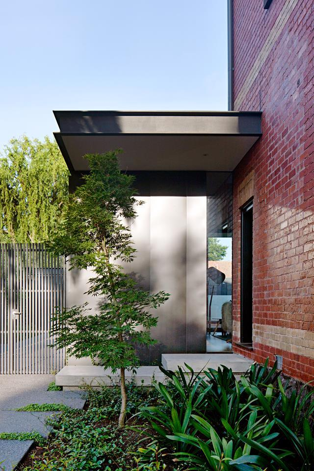 This side entrance assembles materials old and new: red brick and concrete slab steps with a steel and zinc canopy over the side door.