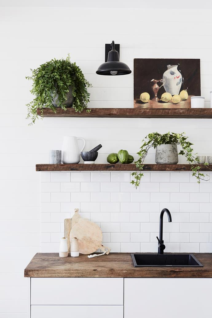 **Use natural timber finishes** Raw, grainy timber shelves and counters lend a rustic feel to the glossy tiles and handle-less joinery in the kitchen. Plants, art, homewares and fresh fruit keep the look casual.