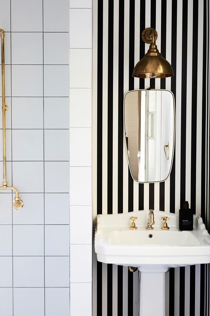 **Coastal meets Deco** Chic striped wallpaper is sophisticated and cheery, with the brass taps and light shade the perfect accompaniment to the Art Deco-style mirror.