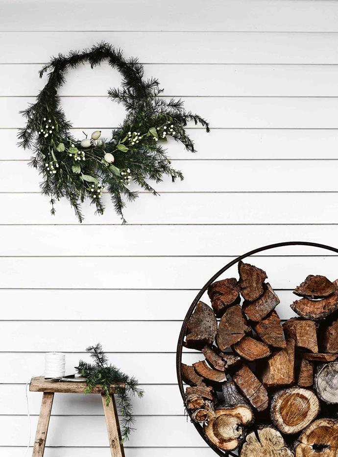 A simple wreath decorates the verandah, well stockpiled with wood. The metal hoop is from Wombat Hill Nursery & Florist in Daylesford.