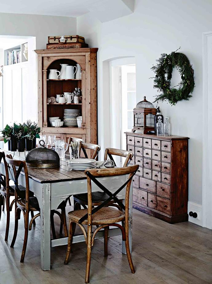 The Georgian corner cabinet from Longford Antiques holds crockery for the dining area, while a festive wreath hangs above an Indonesian birdcage.