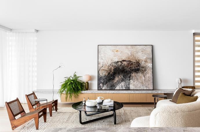 A Sophie Cape artwork commands attention in the living area, flanked by an India Mahdavi table lamp from Studio ALM on one side and a sculpture from Fred International on the other. Flexform side table from Fanuli.