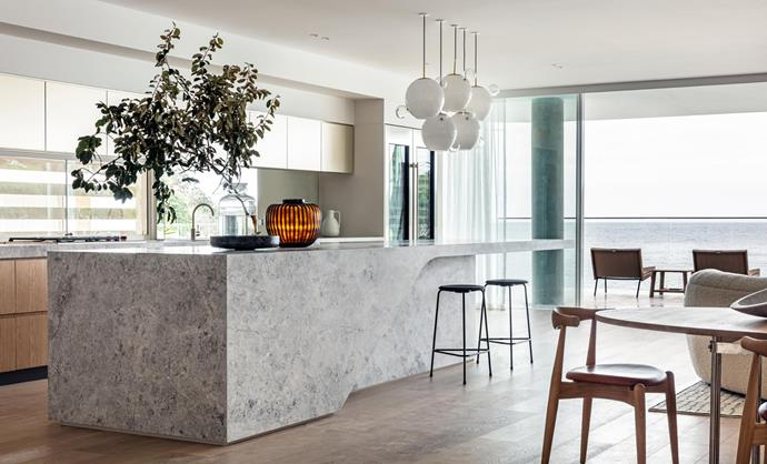 Objects from Ondene and Conley & Co on the island bench, clad in CDK Stone 'Savoir' limestone. The kitchen features Sub-Zero and Wolf appliances, and is finished with 'High Dot' stools from Cult. Carl Hansen & Søn 'CH20 Elbow' chairs surround a 'CH336' table with Poltrona Frau 'Pura' bowl, all from Cult.