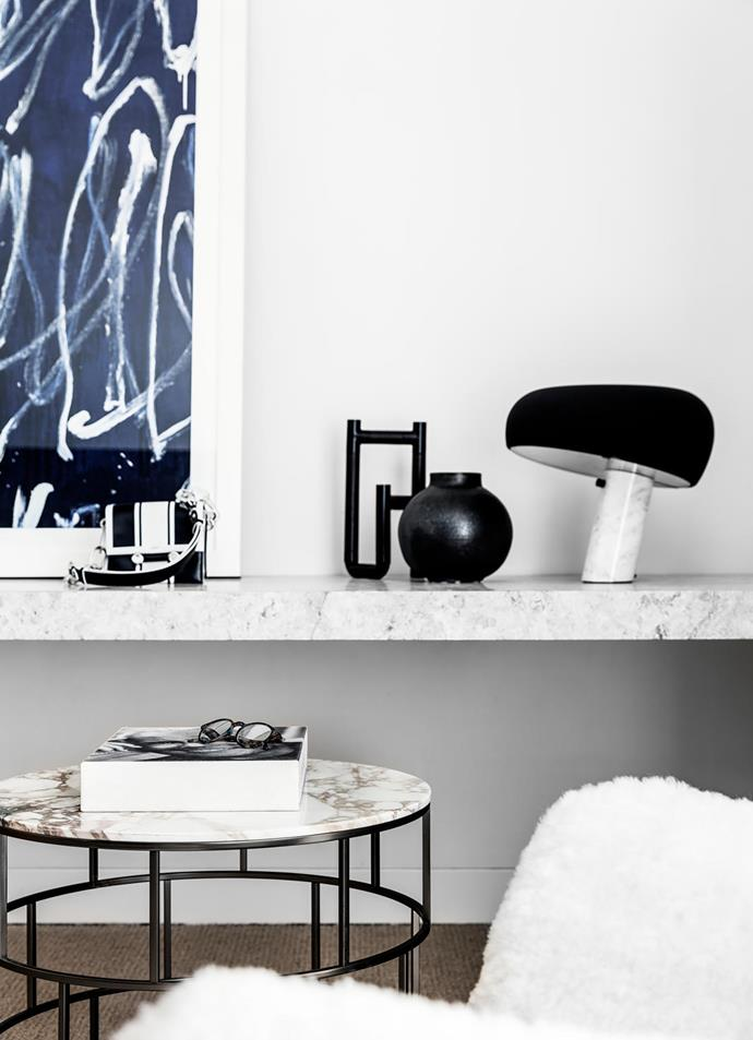 Behind the 'Riviera' table from Fanuli, the marble shelf props up an artwork from MCM House, La Chance candle holder from Living Edge, black vase from Planet, and Flos 'Snoopy' lamp from Euroluce.