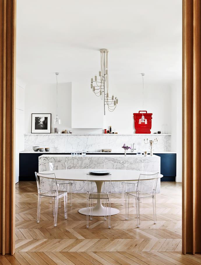 Eero Saarinen dining table with Philippe Starck 'La Marie' chairs in the kitchen. Vintage chandelier by Alain Richard. Two glass ceiling lights by Michele De Lucchi. Red typewriter is an Olivetti advertising board designed by Ettore Sottsass.