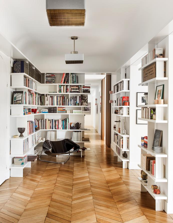 Lined with bookcases designed by Charlotte, the entry hall has vintage ceiling lights by Paavo Tynell. 'Ribbon' chair is a 1961 design by Cesare Leonardi and Franca Stagi for Fiarm.The master bathroom is clad in Carrara marble. Photograph is by Facundo de Zuviria. The 1950s chair was designed by Richard McCarthy.
