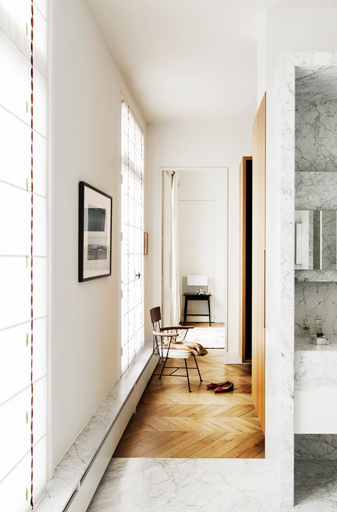 The master bathroom is clad in Carrara marble. Photograph is by Facundo de Zuviria. The 1950s chair was designed by Richard McCarthy.