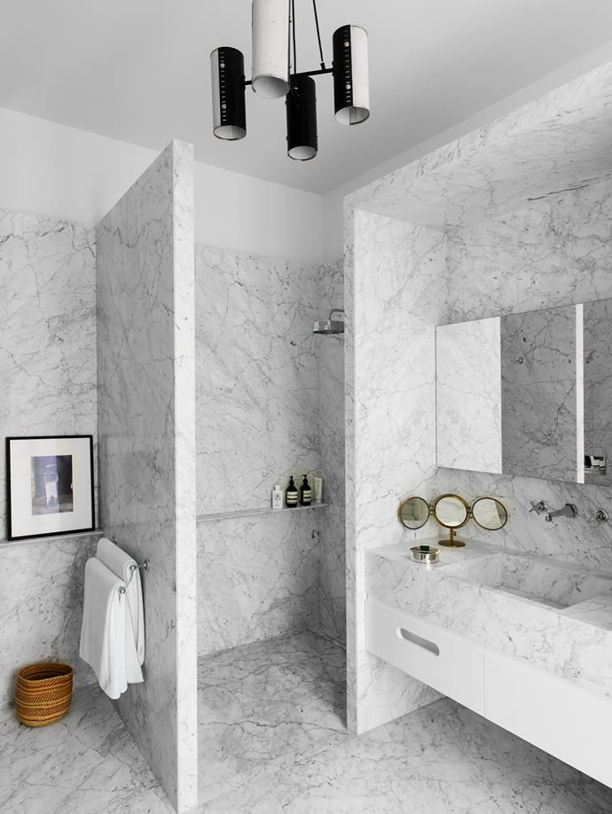 Carrara marble in the master bathroom. Ceiling light was bought at a Paris flea market. Straw basket from Mali. Photograph above is by Graciela Iturbide.