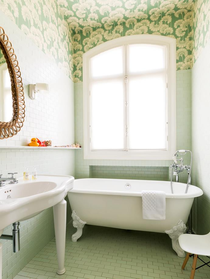 The children's bathroom has 'Japanese Floral' wallpaper by Signature Prints on the ceiling. Vintage wicker mirror came from a Paris flea market. Bathtub from Jacob Delafon. Fittings from Lefroy Brooks.