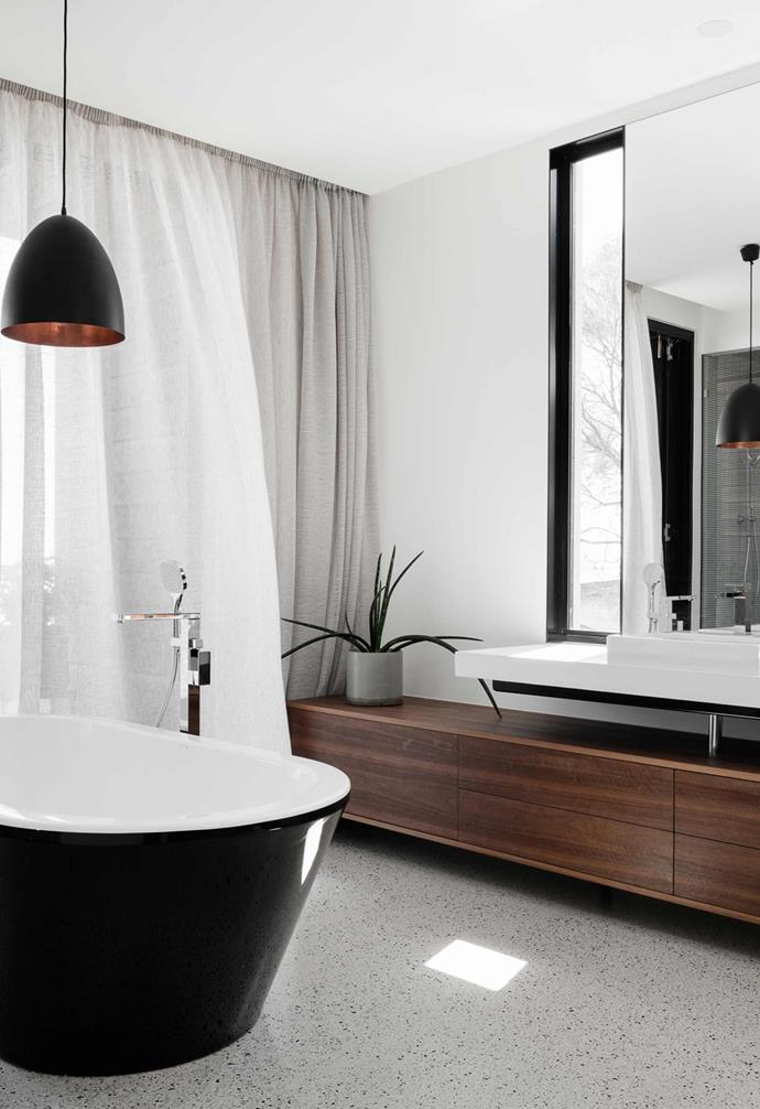 "In the bathroom of this [ultra-modern coastal home](https://www.homestolove.com.au/modern-coastal-house-19462|target=""_blank"") the white palette is broken up by a rich timber sideboard and soft linen curtains."