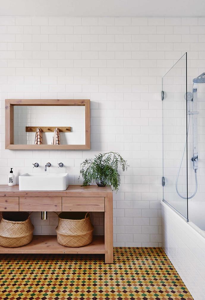 "When this family tackled the renovation of their [Californian bungalow in Barwon Heads](https://www.homestolove.com.au/californian-bungalow-barwon-heads-17909|target=""_blank""), injecting a sense of playfulness and colour throughout the home was of paramount importance. In the bathroom a vibrant patterned yellow floor tile provides a dramatic contrast to the white subway tiles on the walls, as well as the minimalist timber vanity and timber-framed mirror."