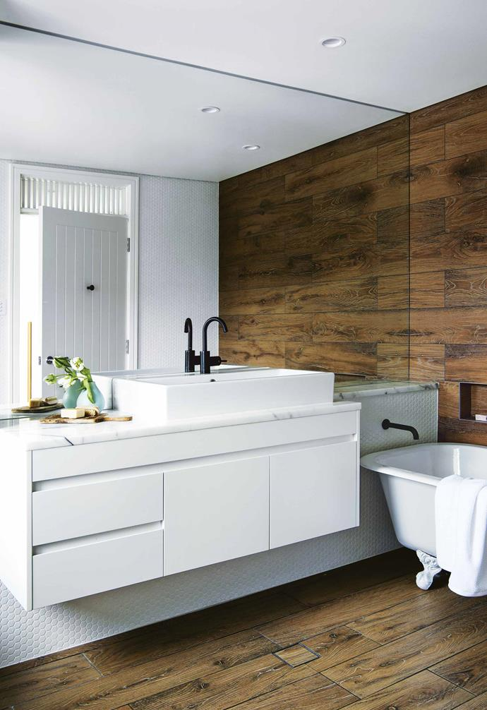 "The bathroom of this [weatherboard home in Freshwater](https://www.homestolove.com.au/eco-friendly-weatherboard-house-freshwater-17440|target=""_blank"") features dark timber floors and a striking timber-lined feature wall. Providing contrast is a white claw-foot bathtub, white tiles and a white-and-marble vanity."