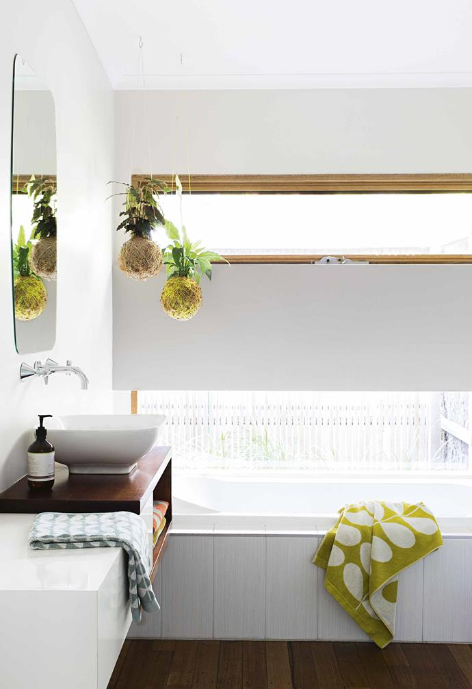 "Seeking to maximise the sense of natural light and space within the bathroom of this [timber-clad sustainable home](https://www.homestolove.com.au/timber-clad-sustainable-house-17545|target=""_blank""), dark timber flooring is paired with all-white walls and ceilings. The white and timber vanity ties the space together."