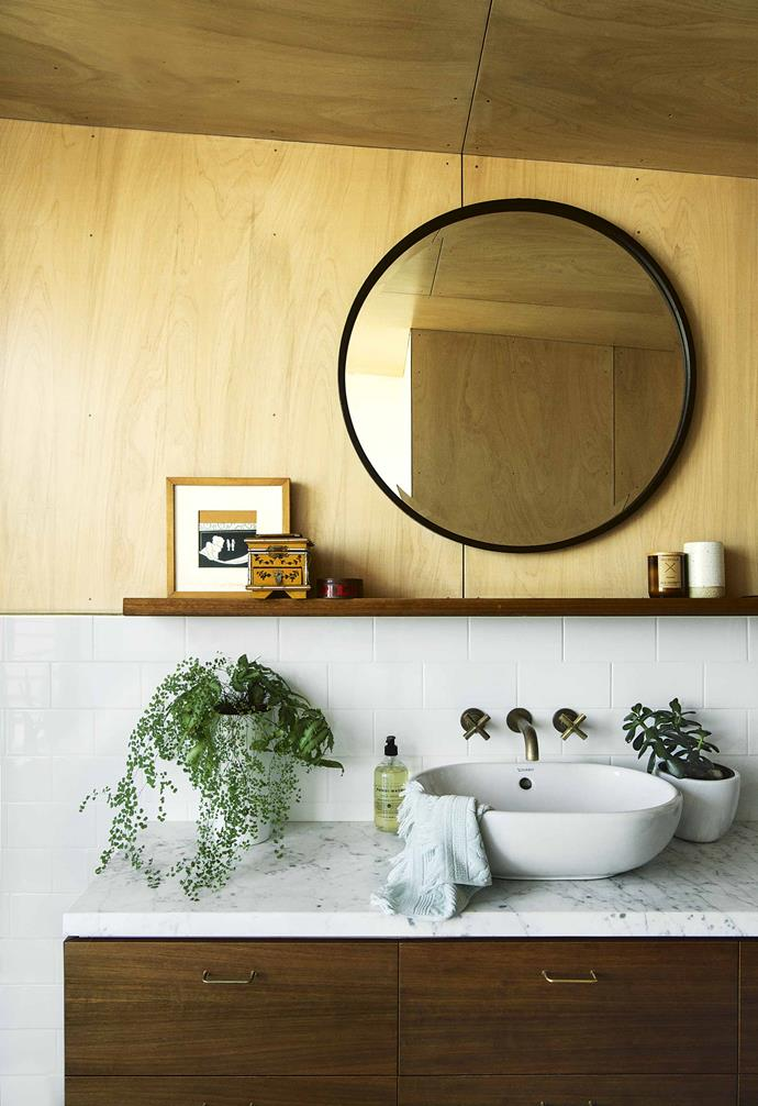 "This [Clovelly beach house](https://www.homestolove.com.au/reverse-brick-veneer-house-18270|target=""_blank"") features a stunning palette of natural materials that extend throughout the entire house. In the bathroom the ceiling and part of the walls are lined in plywood for an organic touch. White subway tiles and a white basin accompany a timber and marble vanity."