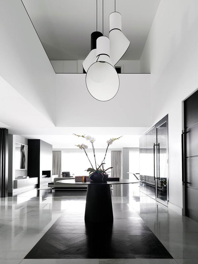 "Contrasting white, bright and open spaces with areas of dark moody glamour lifts the tempo in this [waterfront home](https://www.homestolove.com.au/gold-coast-home-by-architect-bayden-goddard-4607|target=""_blank""). A custom pendant from Boyac hangs over a Moooi table in the double-height space, to draw the eye upwards and bring a vertical focus to the generously sized entry."