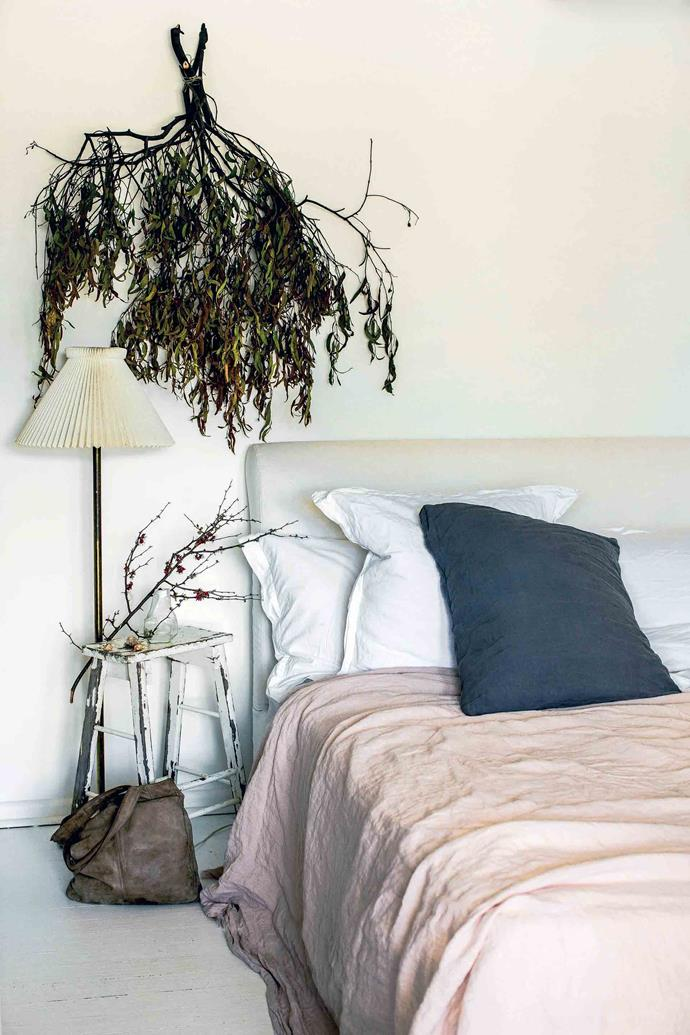 The home's master bedroom is styled simply with foraged foliage and luxurious linen bedding.