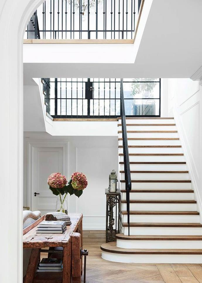 "With its juxtaposition of modern and traditional – a flowing wrought-iron balustrade and classic wall panelling teamed with industrial steel-framed windows and skylight – [this entryway](https://www.homestolove.com.au/gothic-revival-home-19307|target=""_blank"") could belong in a Belle-Époque Parisian townhouse."