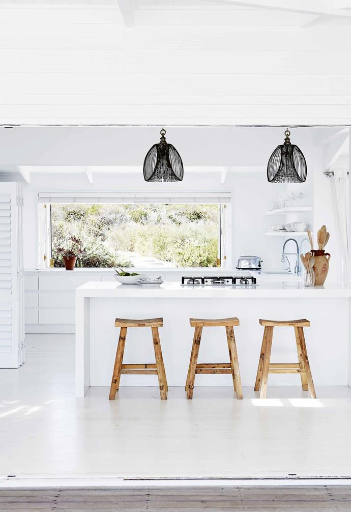 The area is governed by an aesthetic building code that restricts building height to six metres and allows for three styles of house: 'farm' style, 'west coast' style and 'beach' style. Working within these parameters, the couple knew from the start that they wanted to create a contemporary, clapboard-clad timber house that spoke of calm and carefree seaside living.<br><br>**Kitchen** This space, like the rest of the home, is bathed in natural light, which is maximised with the overarching white palette. Despite the commitment to the tone, the home avoids a clinical feel due to the addition of warm timber and textural pendant lights.