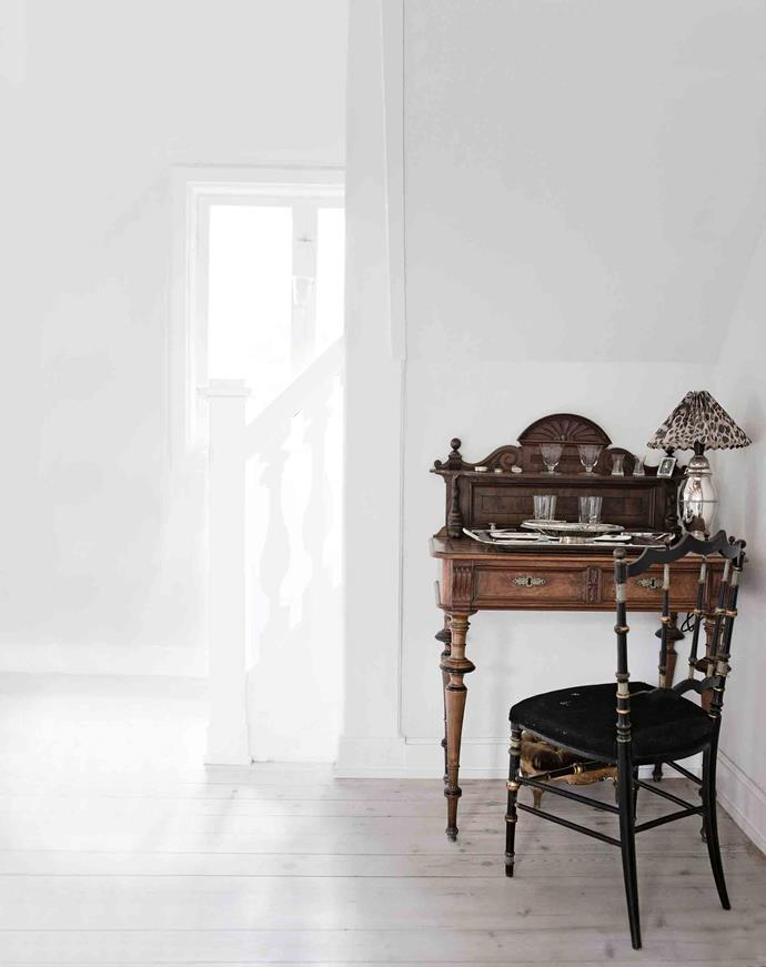 An antique writing desk by the stairs.