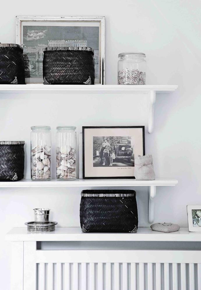 Old photographs and carefully chosen natural objects arranged on bedroom shelves.