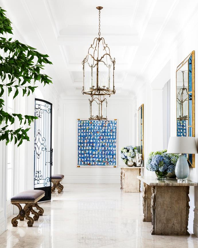 Entry hall walls painted in Resene 'Sea Fog' serve as a pure-white backdrop to a work by Paul Partos. A trip to Dennis & Leen in LA yielded the custom 'Versailles' lanterns, pair of caryatid consoles with honed silver travertine tops, twin 'York' mirrors with blue mirror border, and two 'Sarbonne' benches.