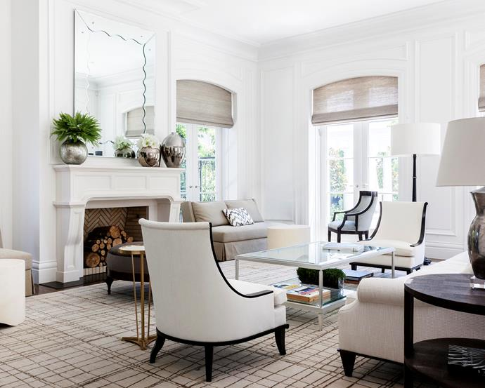 A pair of armchairs from Tyrone Dearing face off in the formal sitting room complemented by twin custom-made sofas and a glass coffee table with a white-gild finish by Thomas Hamel & Associates.