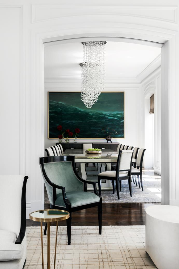 A Tim Storrier seascape is the strength in the formal dining room. Dylan Farrell designed the dining chairs to make a suite with the silver-leaf tables. 'H2O' crystal chandeliers from Zia Priven, LA.