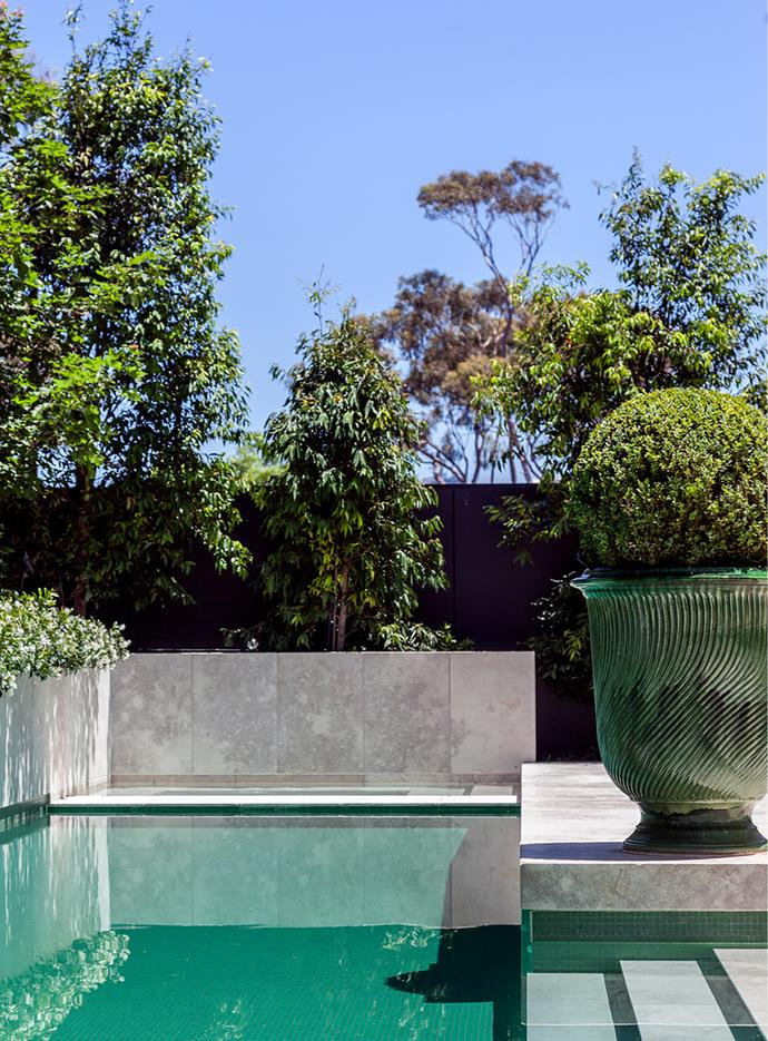 Jasmine spills over the pool's limestone wall. For year-round good looks, landscaper Paul Bangay designed the garden in a restrained green palette. Urn from Graham Geddes Antiques, Melbourne.