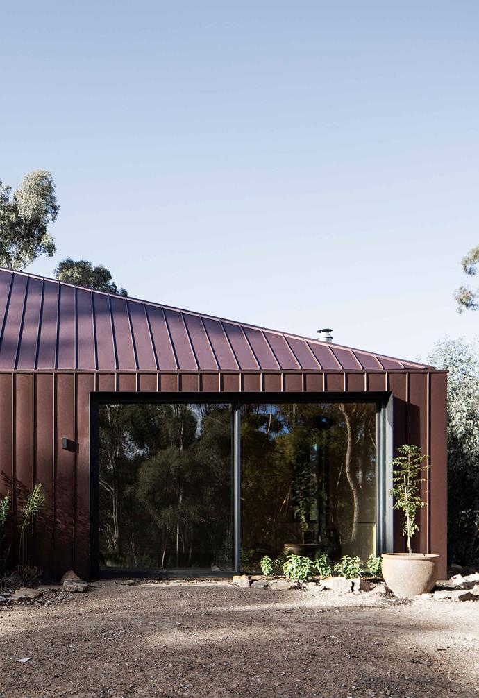 **Exterior** The home is clad in burnished brown metal sheeting to help it meld seamlessly into the rural landscape. Generous windows and sliding doors connect the indoors to the outdoors.