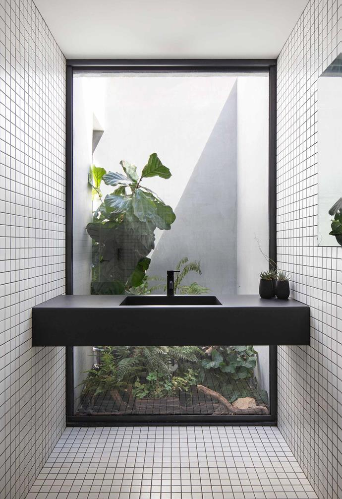 **Bathroom** The shower and bathroom are situated in a concrete 'block' that is attached to the rear of the home. White tiles provide a stark contrast to the concrete and plywood palette in the rest of the home.