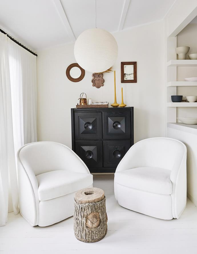 Custom swivel armchairs by Tamsin Johnson upholstered in Dedar fabric from South Pacific Fabrics, rattan mirrors and terracotta wall vase sourced in France, and candles by Tony Assness, all beneath a paper lantern by Isamu Noguchi.