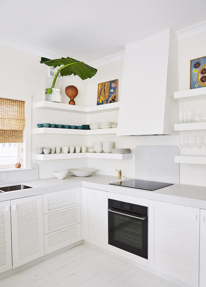 Gabrielle Penfold artworks on the floating kitchen shelves above shutter-fronted joinery with concrete benchtops.