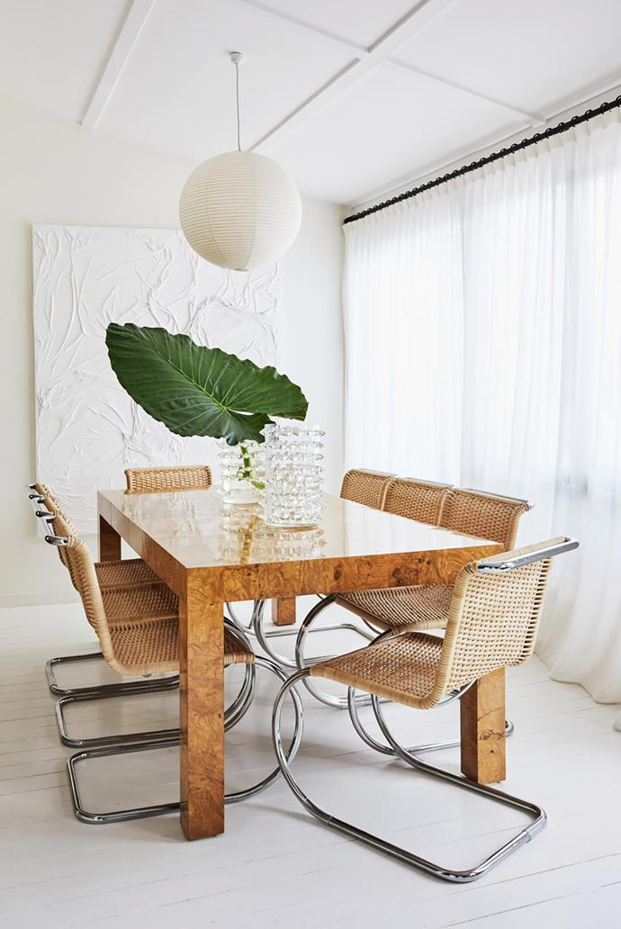 Thonet rattan dining chairs by Ludwig Mies van der Rohe from Anibou surround an olive burlwood table by Milo Baughman topped with Murano vases from Tamsin Johnson. Huseyin Sami artwork from Sarah Cottier Gallery.